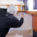 Marilyn working on painting the walls in the cabin that are currently wallpapered.