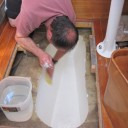 Van working hard on cleaning the oily film off the cured surfaces. This is much easier to do when the tank lid is cut off. Notice the final white coloring of the surface, after we covered the blue spots with another layer of Permaflex and then LRB. Also notice there are no baffles in this large tank. Odd, but we didn't change it.